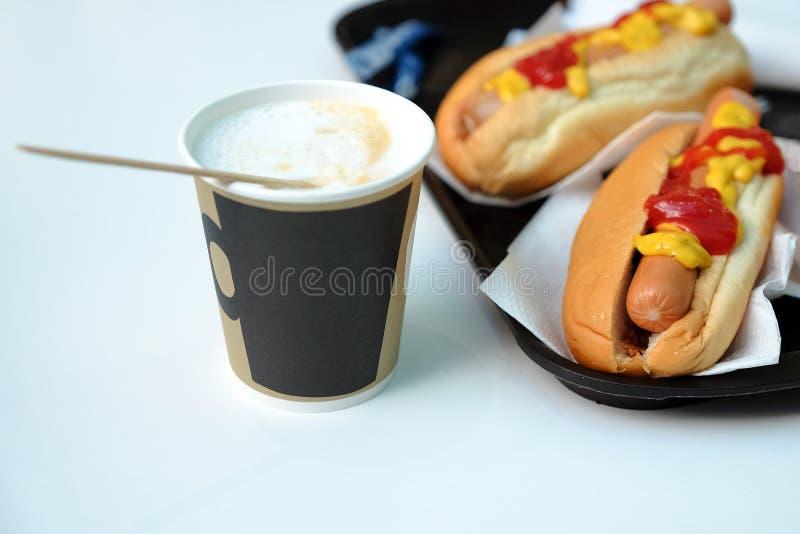 Απλό πρόγευμα σάντουιτς χοτ-ντογκ με το κέτσαπ και τον καφέ μουστάρδας στοκ εικόνα