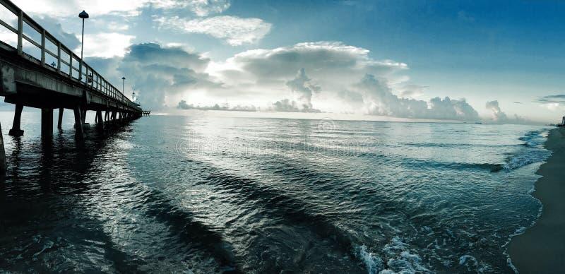 Αποβάθρα και ο ωκεανός με το νεφελώδη μπλε ουρανό στοκ εικόνες