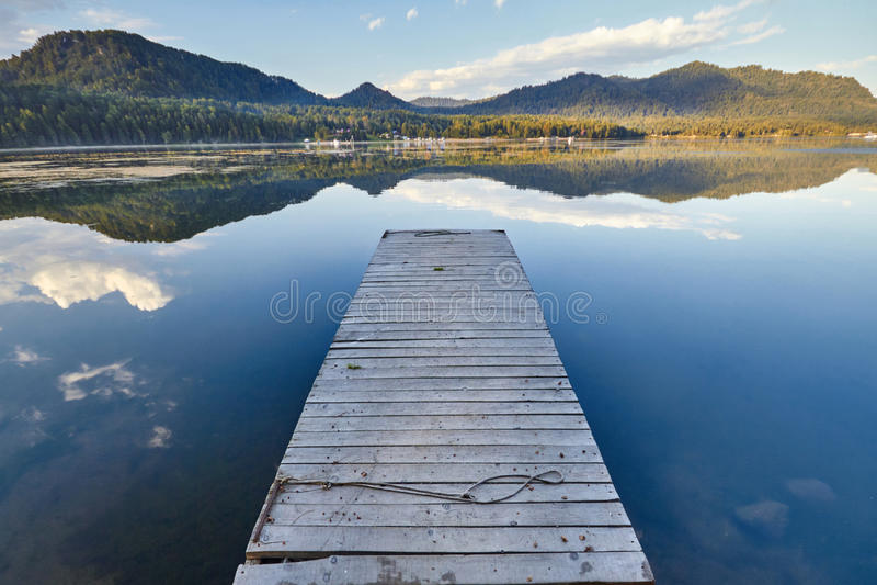 Αποβάθρα στη λίμνη στο υπόβαθρο του ηλιοβασιλέματος σε μια σαφή θερινή ημέρα Θερμό θερινό βράδυ στην αποβάθρα Μυθικές απόψεις της στοκ εικόνες