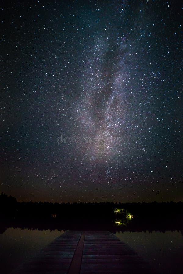 Αποβάθρα στη λίμνη τη νύχτα με το γαλακτώδη τρόπο στο υπόβαθρο στοκ φωτογραφία
