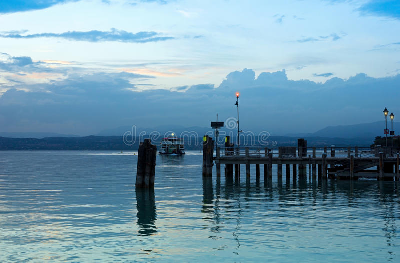 Αποβάθρα Garda λιμνών και το τελευταίο πορθμείο για την ημέρα στοκ φωτογραφίες