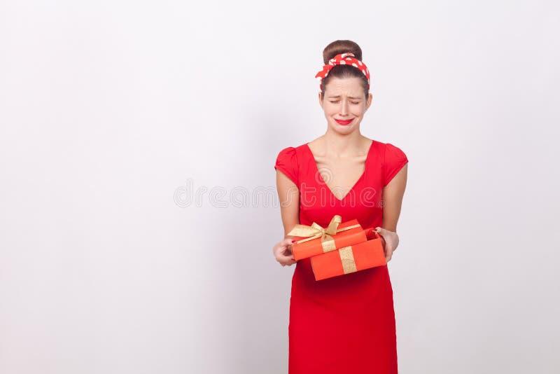 απογοήτευση Γυναίκα που κρατά το κόκκινο κιβώτιο και την κραυγή Κακό δώρο στοκ φωτογραφίες