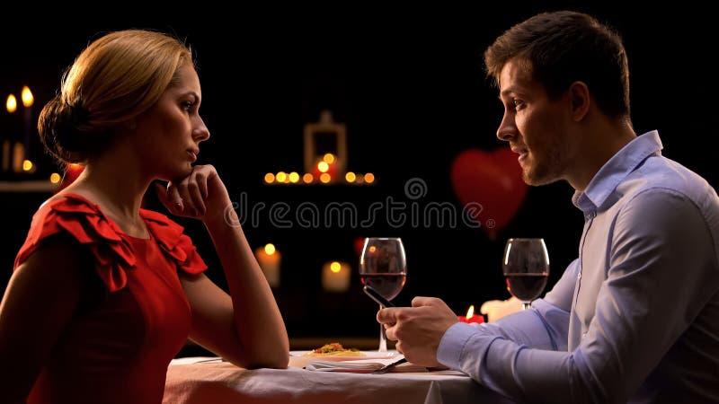 Απογοητευμένη γυναίκα που εξετάζει το φίλο που χρησιμοποιεί το smartphone κατά τη διάρκεια της ρομαντικής ημερομηνίας στοκ εικόνες