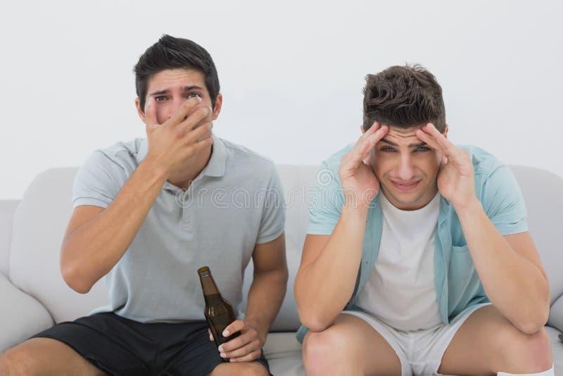 Απογοητευμένοι ανεμιστήρες ποδοσφαίρου που προσέχουν τη TV στοκ φωτογραφία
