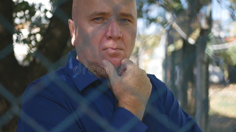 Απογοητευμένος άνθρωπος που σκέφτεται την επιθετική επιστροφή του μεταλλικού φράχτη σε περιοχή προστασίας στοκ εικόνα