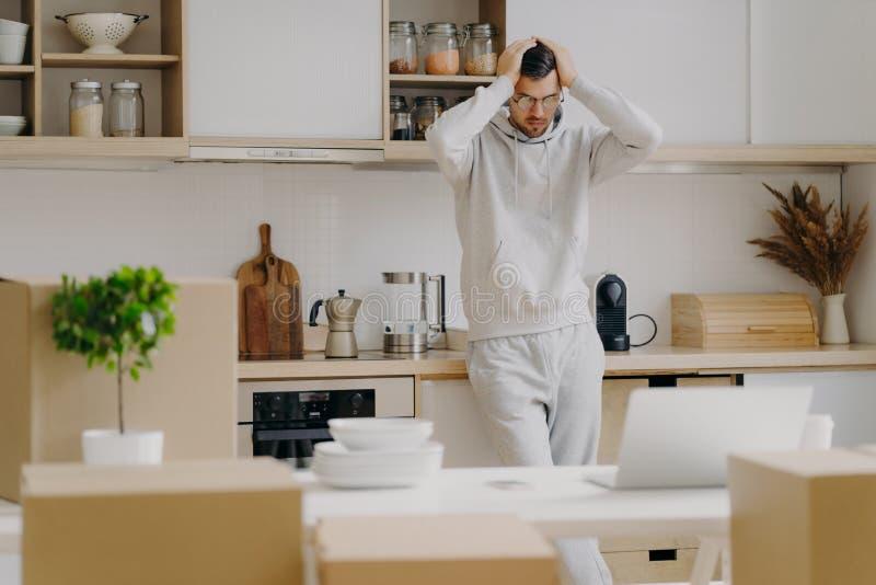 Απογοητευμένος Καυκάσιος αντιμετωπίζει οικονομικά προβλήματα, ενοικιάζει νέο διαμέρισμα, κοιτάει με απορία τον φορητό υπολογιστή, στοκ φωτογραφίες με δικαίωμα ελεύθερης χρήσης