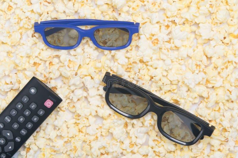 αποκαλυμμένο τηγανισμένο popcorn, κινηματογράφηση σε πρώτο πλάνο, ως υπόβαθρο με ένα ζευγάρι των τρισδιάστατων γυαλιών και ενός τ στοκ εικόνες