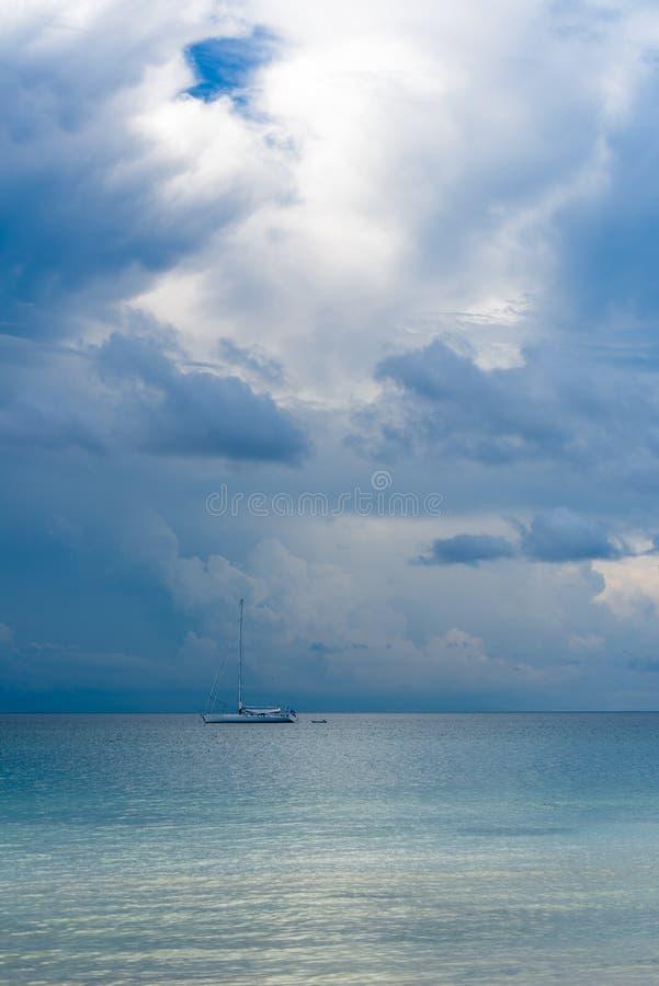 Αποκλειστικό μεγάλο άσπρο γιοτ που κολυμπά στη θάλασσα με τα θυελλώδη σύννεφα στο υπόβαθρο στοκ εικόνα