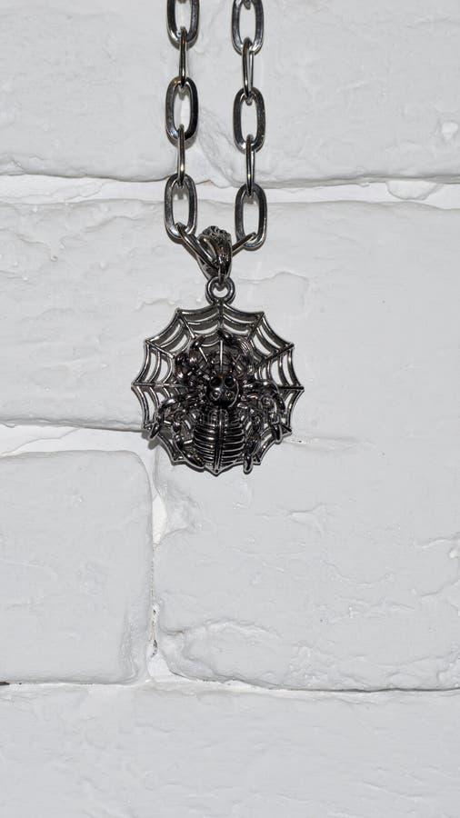 Αποκριές η ένωση αραχνών ένωσης σε μια αλυσίδα σε έναν άσπρο τοίχο πετρών στοκ εικόνα