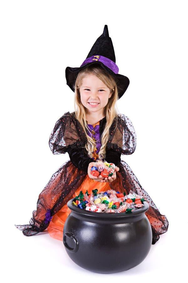 Αποκριές: Η μάγισσα κοριτσιών σκάβει στο δοχείο αποκριών Goodies στοκ φωτογραφίες