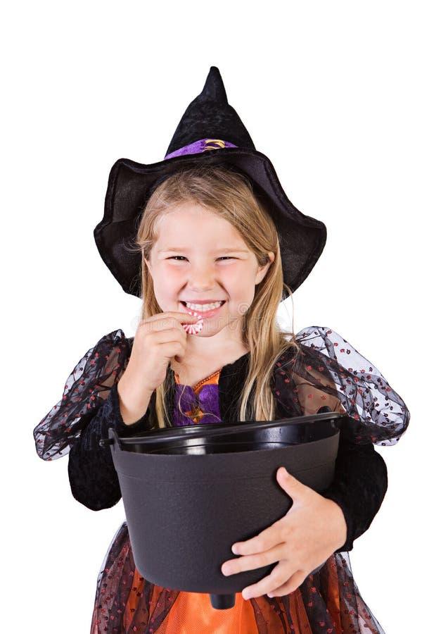 Αποκριές: Η μάγισσα κοριτσιών τρώει το κομμάτι της καραμέλας από τον κάδο στοκ εικόνες με δικαίωμα ελεύθερης χρήσης