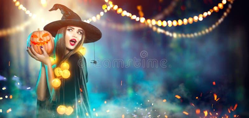 αποκριές Μάγισσα με μια χαρασμένη κολοκύθα και μαγικά φω'τα στοκ εικόνα με δικαίωμα ελεύθερης χρήσης