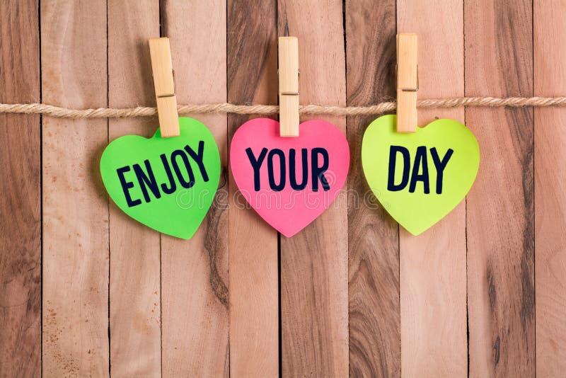 Απολαύστε διαμορφωμένη την καρδιά σημείωση ημέρας σας στοκ φωτογραφίες
