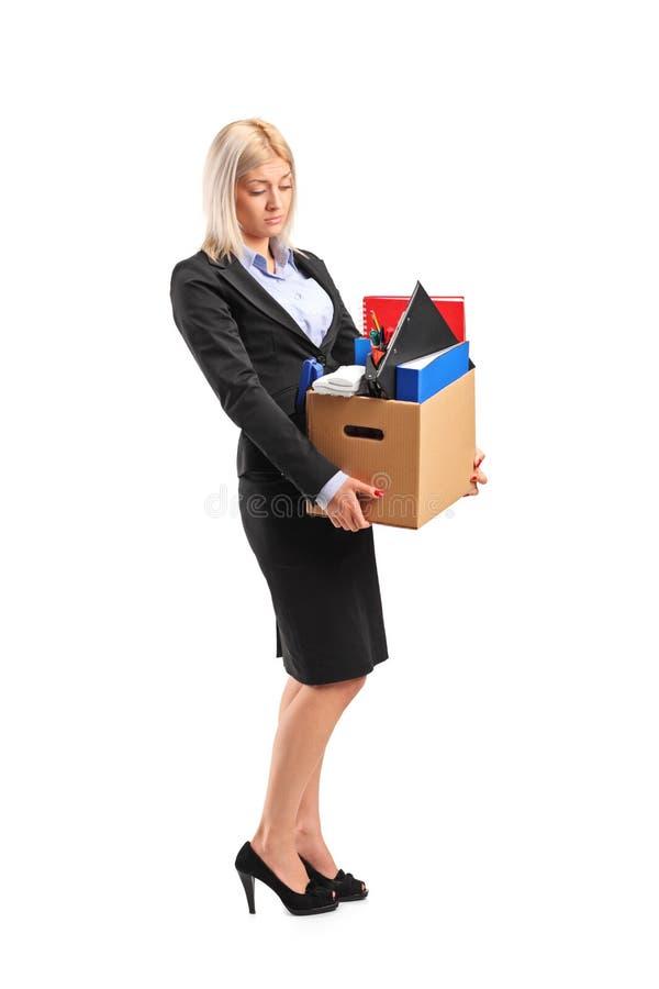 Απολυθείσα επιχειρηματίας σε ένα κοστούμι που φέρνει ένα κιβώτιο στοκ εικόνα