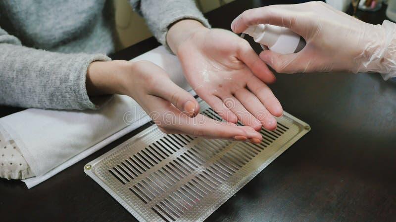 Απολύμανση των χεριών πελατών ` s Χέρια γυναικών ` s στις διαδικασίες μανικιούρ στοκ εικόνες