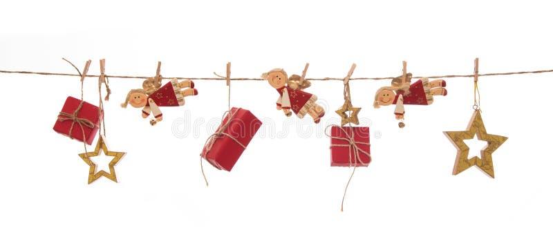 Απομονωμένα κρεμώντας κόκκινα δώρα Χριστουγέννων, άγγελοι και χρυσά αστέρια επάνω στοκ εικόνες