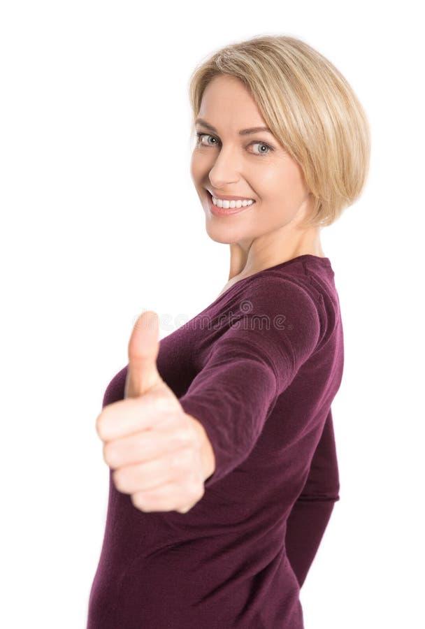 Απομονωμένη ευτυχής ηλικιωμένη ξανθή γυναίκα με τον αντίχειρα επάνω στη χειρονομία στοκ εικόνες