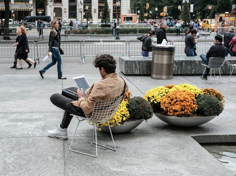 Απομονωμένη νέα βλέπω? αρσενικό συνεδρίαση στην πόλη της Νέας Υόρκης, που εξετάζει έναν υπολογιστή ταμπλετών στοκ φωτογραφία