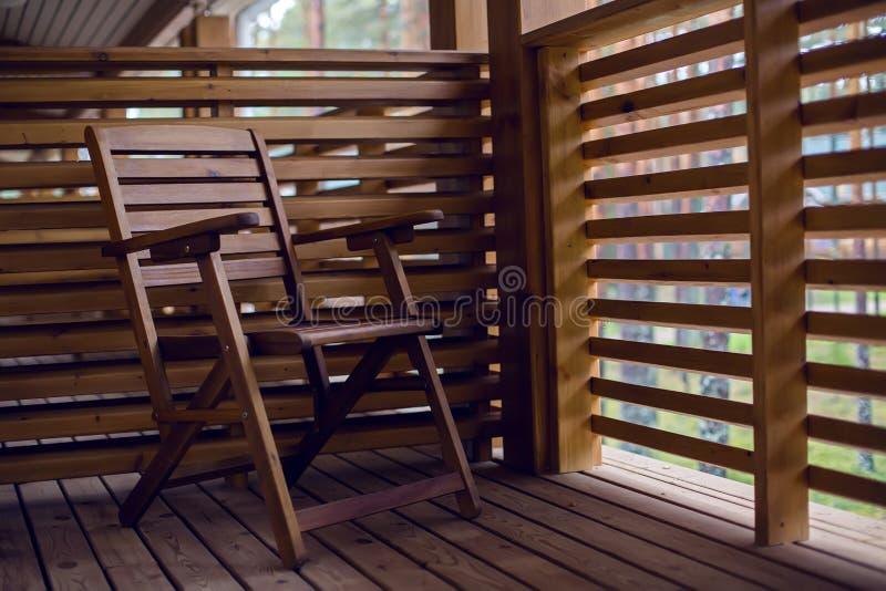 Απομονωμένη ξύλινη καρέκλα στο μπαλκόνι του ξύλου με τα διαφράγματα στοκ εικόνες