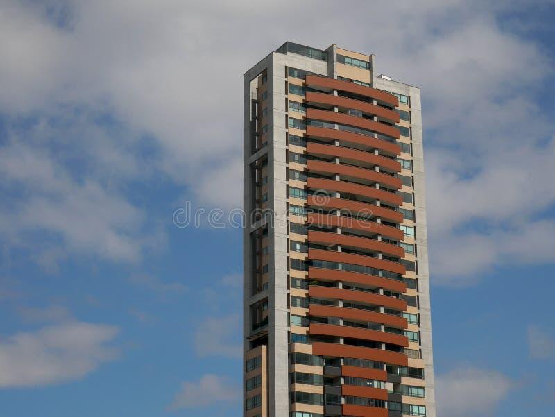Απομονωμένη ψηλή πολυκατοικία πέρα από ένα νεφελώδες διάστημα αντιγράφων μπλε ουρανού στοκ εικόνες με δικαίωμα ελεύθερης χρήσης