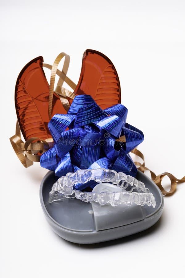 Απομονωμένος διαφανής ευθυγραμμιστής προσθέσεων δοντιών με το κιβώτιο και τον μπλε τρόπο τόξων του Α να έχει ένα όμορφο χαμόγελο στοκ φωτογραφία
