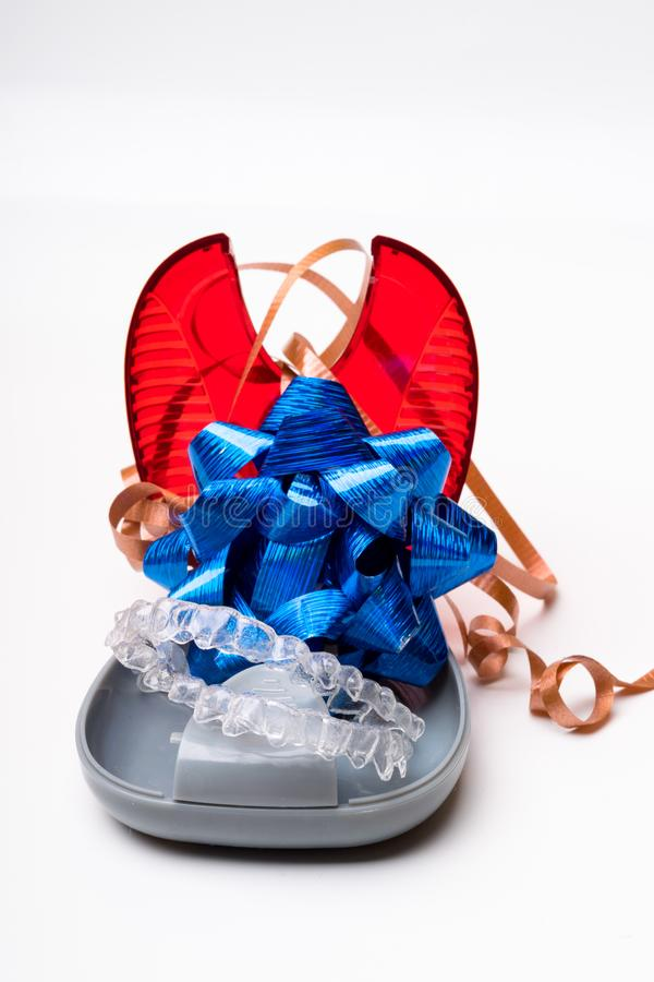 Απομονωμένος διαφανής ευθυγραμμιστής προσθέσεων δοντιών με το κιβώτιο και τον μπλε τρόπο τόξων Α δώρων του να έχει ένα όμορφο χαμ στοκ εικόνα με δικαίωμα ελεύθερης χρήσης