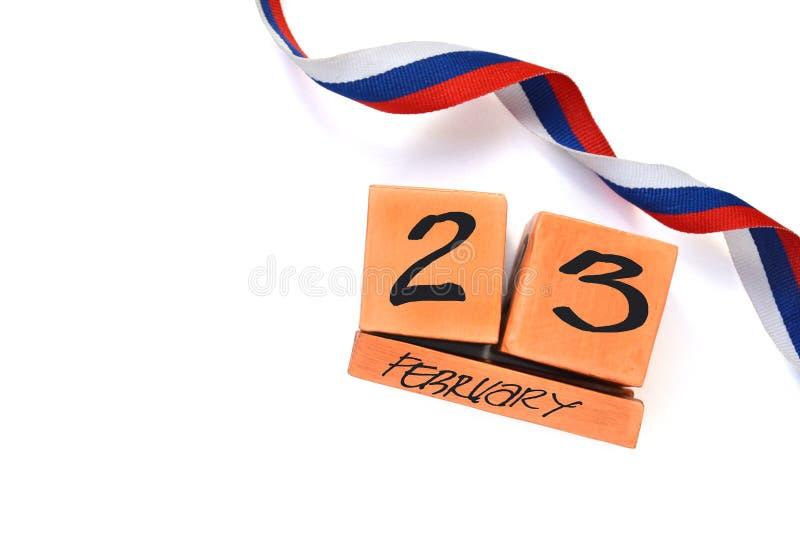 Απομονωμένο διαρκές ξύλινο ημερολόγιο με την ημερομηνία της ρωσικής σημαίας tricolor της 23ης Φεβρουαρίου και κορδελλών στο άσπρο στοκ εικόνα
