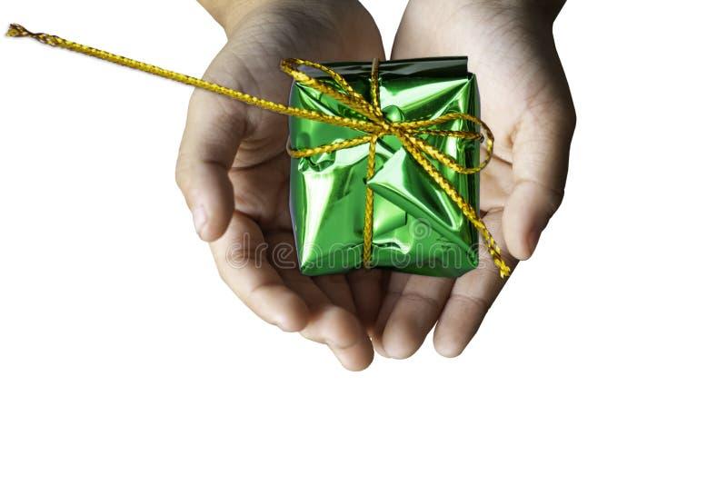 Απομονωμένο κιβώτιο δώρων εκμετάλλευσης χεριών πράσινο για τους εορτασμούς σε ένα wh στοκ φωτογραφίες