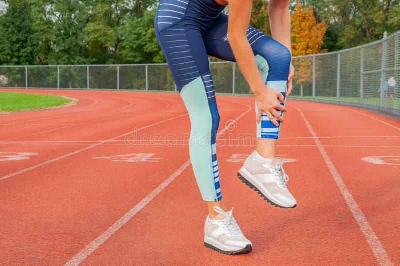 απομονωμένο λευκό ποδιών ανασκόπησης ζημία Ο δρομέας γυναικών που πάσχει από τον πόνο στο πόδι μετά από το workout αγγίζει τον ασ στοκ φωτογραφία
