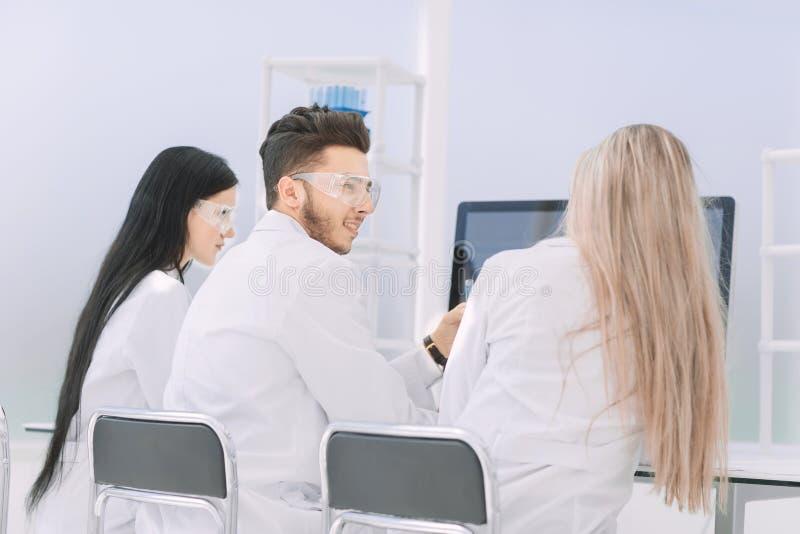 απομονωμένο οπισθοσκόπο λευκό μια ομάδα επιστημόνων εξετάζει το όργανο ελέγχου υπολογιστών στοκ φωτογραφίες με δικαίωμα ελεύθερης χρήσης