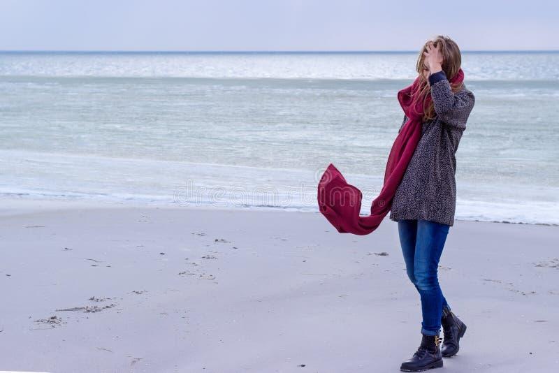Απομονωμένο λυπημένο όμορφο κορίτσι που περπατά κατά μήκος της ακτής της παγωμένης θάλασσας μια κρύα ημέρα, ερυθρά, κοτόπουλο με  στοκ εικόνες