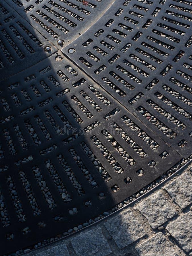 Αποξήρανση θύελλας πεζοδρομίων στο πεζοδρόμιο Αγωγός νερού κατά μήκος μιας οδού στοκ φωτογραφία