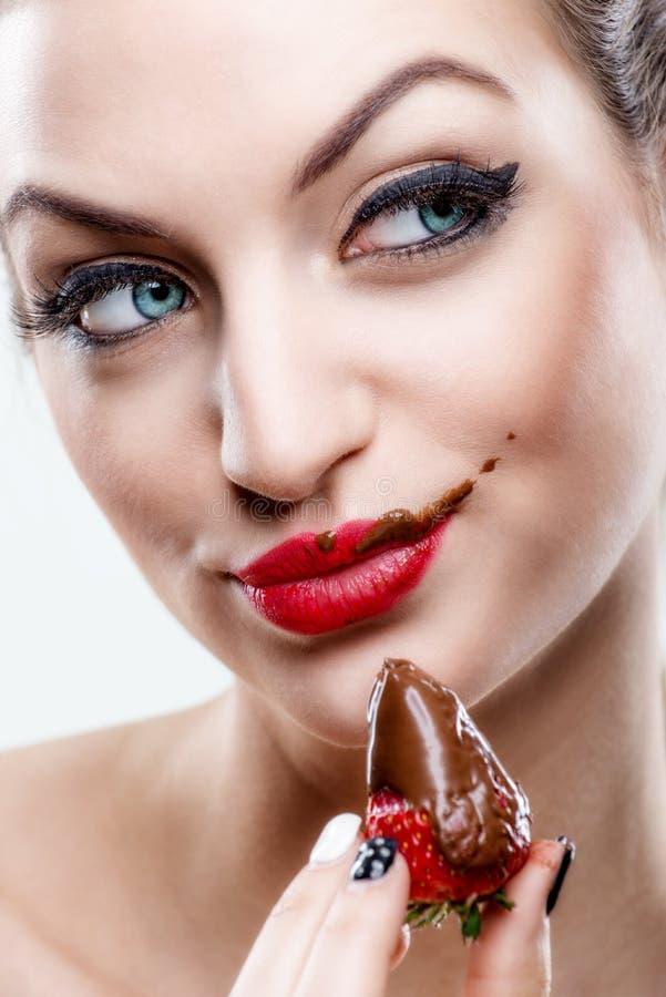 Αποπλάνηση - η ελκυστική γυναίκα που τρώει μια φράουλα, σοκολάτα έγινε το πρόσωπο από την στοκ εικόνες
