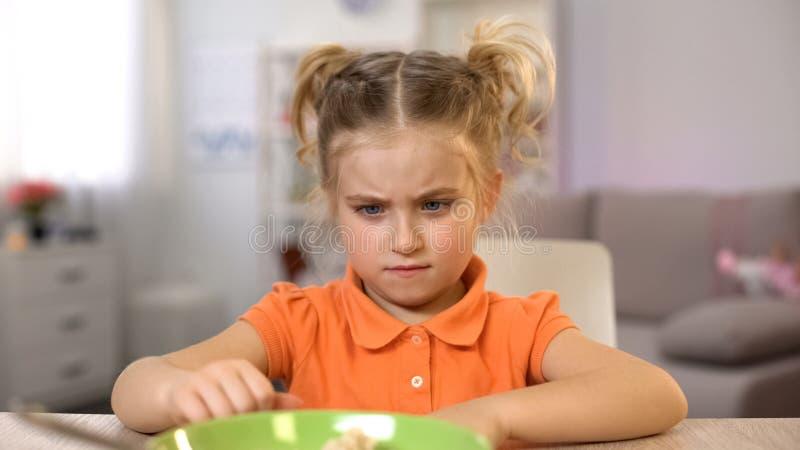 Απορρίματα κοριτσιών που τρώνε το πρόγευμα, που ωθεί το κύπελλο μακριά, υγιής διατροφή παιδιών στοκ εικόνες