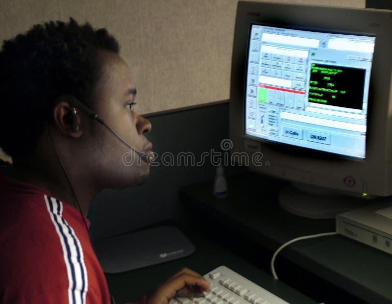 Αποστολέας αστυνομίας που χρησιμοποιεί έναν υπολογιστή για να αποστείλει τις μονάδες στις κλήσεις για τη βοήθεια στοκ φωτογραφία με δικαίωμα ελεύθερης χρήσης