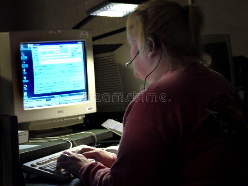 Αποστολέας αστυνομίας που χρησιμοποιεί έναν υπολογιστή για να αποστείλει τις μονάδες στις κλήσεις για τη βοήθεια στοκ φωτογραφία