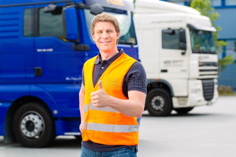 Αποστολέας μπροστά από τα φορτηγά σε μια αποθήκη στοκ εικόνα με δικαίωμα ελεύθερης χρήσης