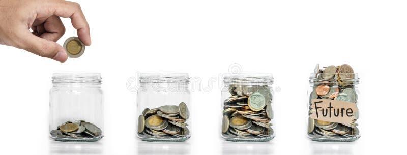 Αποταμίευση χρημάτων, χέρι που βάζει το νόμισμα στο βάζο γυαλιού με τα νομίσματα μέσα να μεγαλώσει, στο άσπρο υπόβαθρο, την έννοι στοκ φωτογραφία