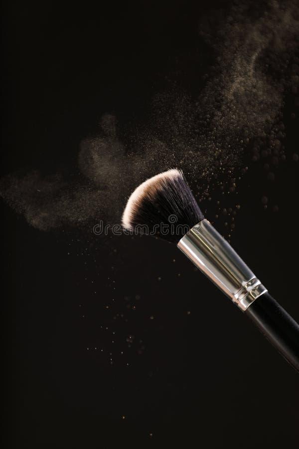 Αποτελέστε τις καλλυντικές βούρτσες με τη σκόνη να κοκκινίσουν έκρηξη στο μαύρο υπόβαθρο στοκ εικόνα