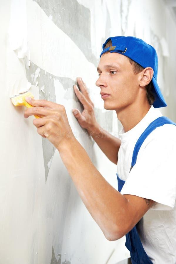 Αποφλοίωση εργαζομένων ζωγράφων από την ταπετσαρία στοκ φωτογραφίες