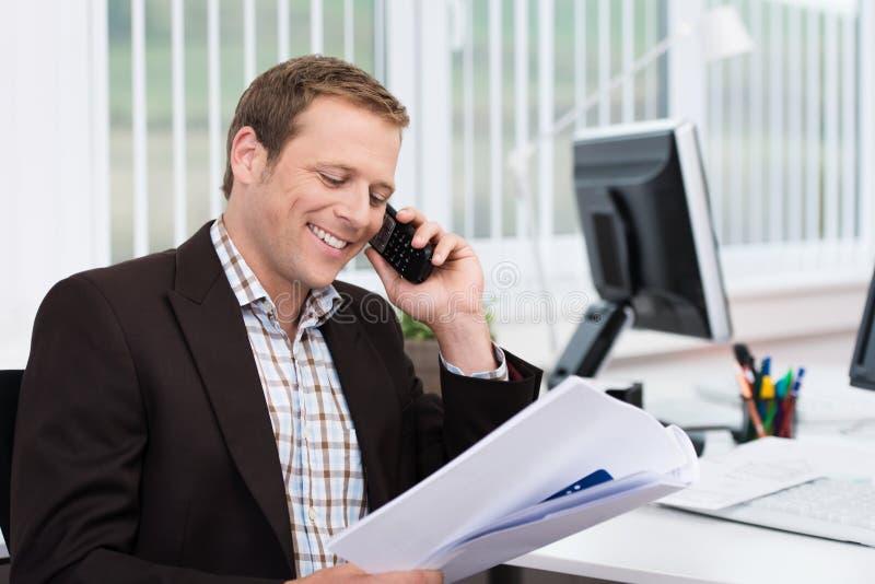 Αποδοτικός επιχειρηματίας που απαντά σε ένα τηλεφώνημα στοκ εικόνα