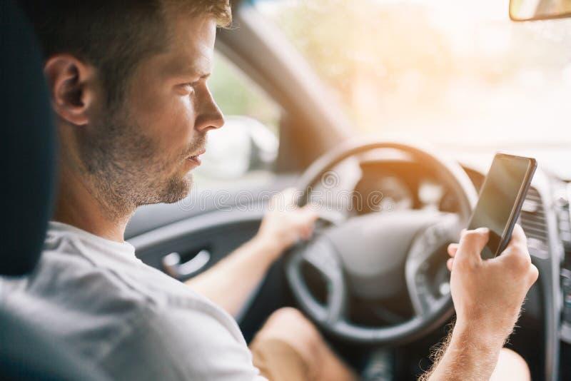 Απρόσεκτος οδηγός που χρησιμοποιεί ένα κινητό τηλέφωνο ταυτόχρονα οδηγώντας στοκ φωτογραφία