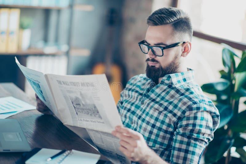 Απρόσεκτος συγκεντρωμένος έξυπνος γενειοφόρος τύπος που ντύνεται στον περιστασιακό έλεγχο στοκ φωτογραφία