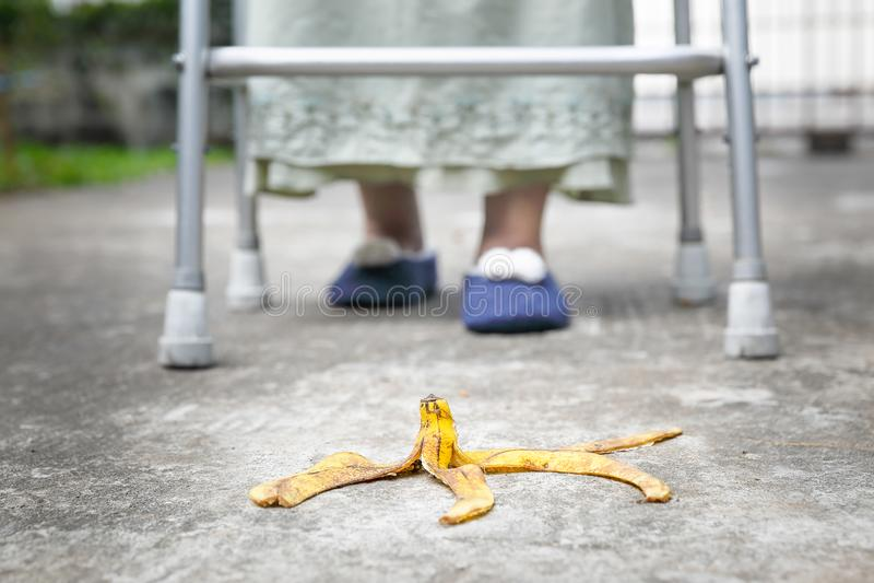 Απρόσεκτο ηλικιωμένο βήμα γυναικών πέρα από μια φλούδα μπανανών στοκ φωτογραφία