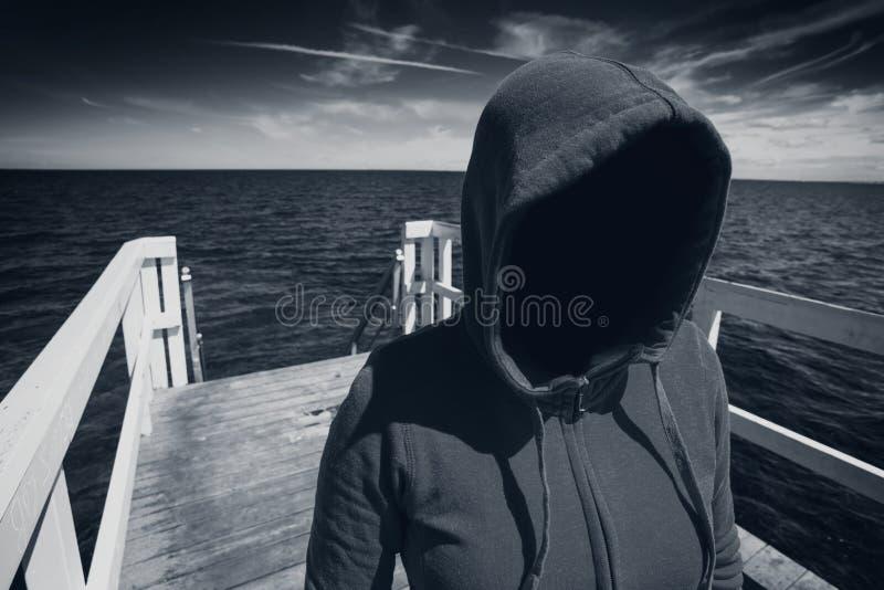 Απρόσωπη με κουκούλα Unrecognizable γυναίκα στην ωκεάνια αποβάθρα, κοβάλτιο απαγωγής στοκ εικόνα με δικαίωμα ελεύθερης χρήσης