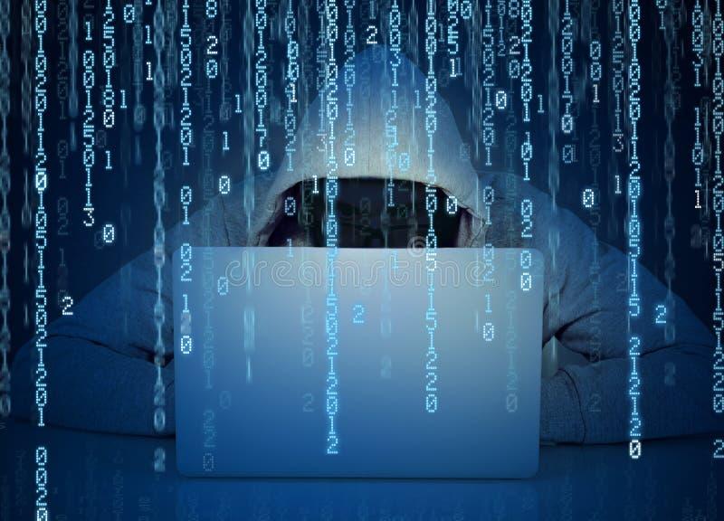 Απρόσωπος χάκερ ατόμων που εργάζεται σε ένα lap-top σε ένα υπόβαθρο δυαδικού κώδικα στοκ εικόνα με δικαίωμα ελεύθερης χρήσης