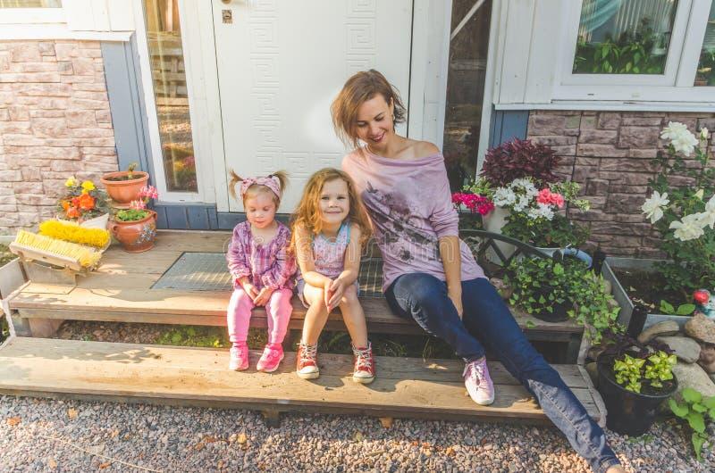 Απόγευμα mom και δύο κόρες στο κατώφλι του σπιτιού στοκ φωτογραφία