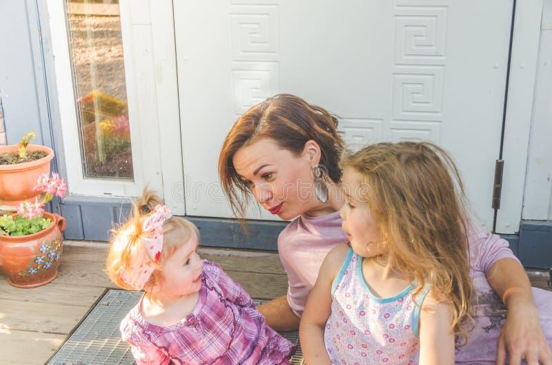 Απόγευμα mom και δύο κόρες στο κατώφλι του σπιτιού στοκ εικόνες