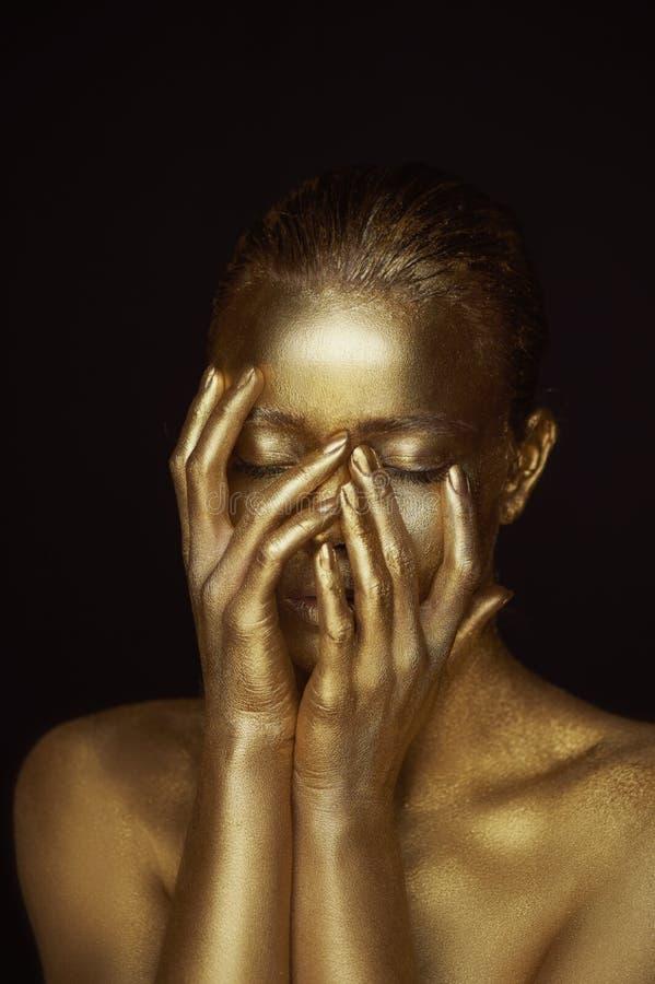 Απόκοσμα χρυσά κορίτσια πορτρέτου, χέρια κοντά στο πρόσωπο Πολύ λεπτός και θηλυκός Τα μάτια είναι κλειστά στοκ φωτογραφίες με δικαίωμα ελεύθερης χρήσης