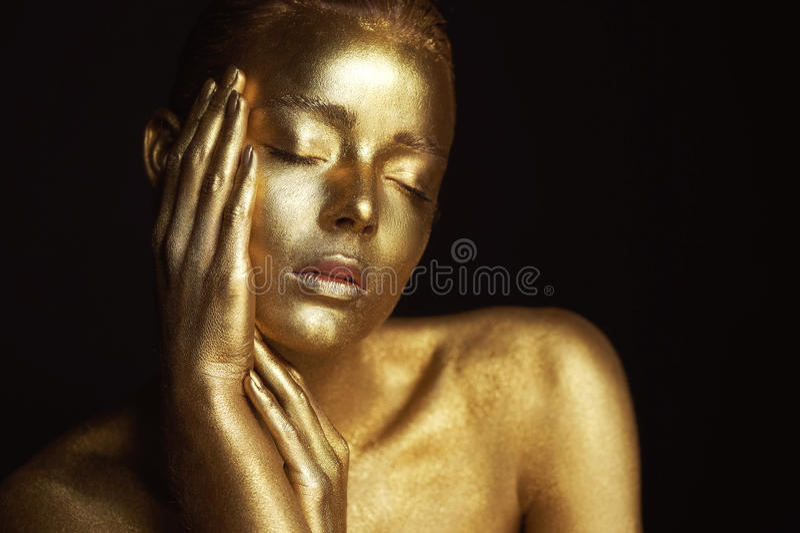 Απόκοσμα χρυσά κορίτσια πορτρέτου, χέρια κοντά στο πρόσωπο Πολύ λεπτός και θηλυκός Τα μάτια είναι κλειστά στοκ φωτογραφία
